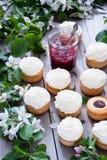 Muffin med smör lagar mat med grädde och fjädrar vita blommor Fotografering för Bildbyråer