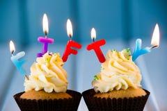 Muffin med stearinljus för 50 - femtionde födelsedag Arkivfoton