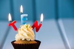 Muffin med stearinljus för 10 - tionde födelsedag Arkivbild