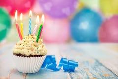 Muffin med stearinljus på partiet för födelsedagberöm Arkivfoto