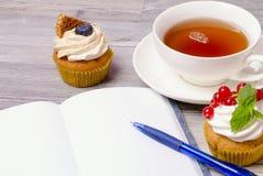 Muffin med te och anteckningsboken Arkivbilder