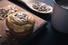 Muffin, Mischsamen und Schale Milch auf schwarzem Hintergrund stockfotografie