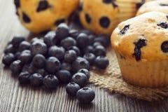 Muffin mit Blaubeeren auf einem Holztisch frische Beeren und süßes Gebäck auf dem Brett stockbilder