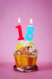Muffin mit brennenden Geburtstagskerzen als Nr. achtzehn Lizenzfreies Stockbild