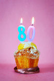 Muffin mit brennenden Geburtstagskerzen als Nr. achtzig Lizenzfreies Stockfoto