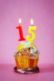 Muffin mit brennenden Geburtstagskerzen als Nr. fünfzehn lizenzfreie stockfotos