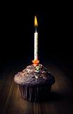 Muffin mit brennender Kerze Stockfotos