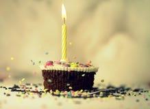 Muffin mit Kerze und besprüht Stockfotografie