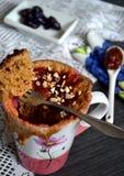 Muffin mit Pflaumensoße kochte in einem Mikrowellenherd in der rosa und weißen Schale Stockfoto