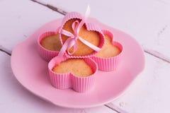 Muffin nelle forme rosa per cuocere (sotto forma di cuore) Fotografie Stock