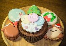 Muffin och Macarons med älskvärt julpynt under julfestival Arkivbilder