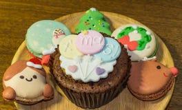 Muffin och Macarons med älskvärt julpynt under julfestival Arkivbild