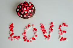 Muffin och ord FÖRÄLSKELSE med små hjärtor Royaltyfri Bild
