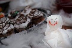 Muffin och spöke med choklad och kräm Arkivfoto
