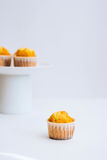 Muffin più arancio in un supporto del dolce Immagini Stock