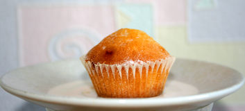 Muffin on Plate. Small muffin in baking paper placed in center of plate Stock Photo
