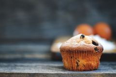 Muffin. With raisins sprinkled with powdered sugar on a wooden background and are ingridient on the back of a blurry background and copy space royalty free stock photo