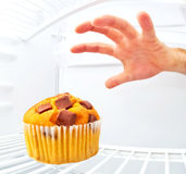 Muffin in a refrigerator. A hand grabs a muffin in a refrigerator Royalty Free Stock Photos
