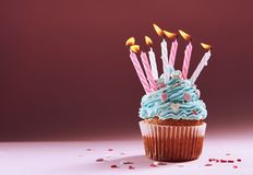 Muffin or a small cake with a burning candle. concept of congratulation, holiday.  Royalty Free Stock Images