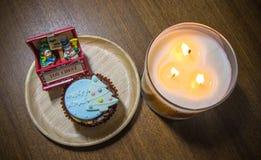 Muffin som överträffas med älskvärt julpynt och stearinljusljus under julfestival Arkivbild
