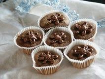 Muffin som överträffas med chokladglasyr på kakablommor Royaltyfri Bild