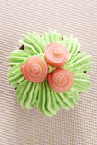 Muffin som dekoreras med isläggning och rosor Arkivfoto