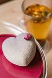 Muffin sotto forma di cuore con zucchero in polvere su un fondo di legno Tè verde della tazza Immagini Stock