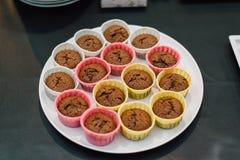 Muffin su una gente della borsa della pasticceria del piatto Fotografie Stock