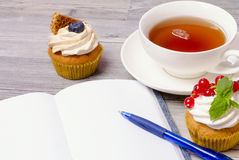 Muffin with tea and notebook Stock Images