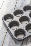 Muffin tray on wooden table Stock Images