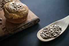 Muffin und Löffel von Mischsamen auf grauem Hintergrund stockfotos