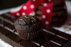 Muffin- und Schokoladensplitterplätzchen mit Schokoriegel und roter silk Bogen mit weißen Punkten Stockfotografie