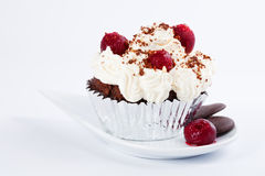 Muffin with whipped cream, cherries and crumbs. Muffin in a container with whipped cream, cherries and crumbs on top on a white modern ceramic plate Stock Photo