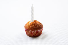 Muffin and white candle. Cupcake with a birthday candle on a white background Royalty Free Stock Photos