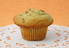 Muffin on white paper. Muffin with nut on white decorative paper over an orange tablecloth Royalty Free Stock Image