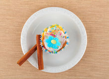 Muffin on a white plate. Muffin and cinnamon stick, on a white plate Royalty Free Stock Images