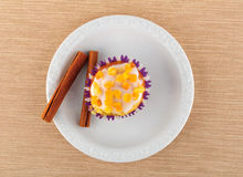 Muffin on a white plate. Muffin and cinnamon stick, on a white plate Stock Photo