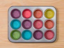 Muffinbakplåt med färgglade pappers- fall arkivbild