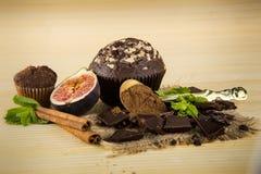 Muffins κινηματογραφήσεων σε πρώτο πλάνο, σοκολάτα, σύκα, σκόνη κανέλας, μεντών και κακάου Στοκ Εικόνες