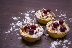 Muffins με τα κεράσια και τα κονιοποιημένα τσιπ ζάχαρης και σοκολάτας επάνω στοκ εικόνες