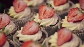 Muffins με τη φράουλα βρίσκονται στο φραγμό καραμελών, κινηματογράφηση σε πρώτο πλάνο φιλμ μικρού μήκους