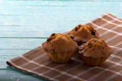 Muffins με τις σταφίδες σε μια ελεγμένη πετσέτα σε ένα μπλε υπόβαθρο Στοκ φωτογραφία με δικαίωμα ελεύθερης χρήσης