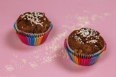 Muffins μπανανών που ψεκάστηκαν με το σουσάμι στο ουράνιο τόξο χρωμάτισαν τα φλυτζάνια ψησίματος στο ρόδινο υπόβαθρο στοκ εικόνες