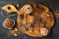 Muffins σοκολάτας και σοκολάτα σε έναν παλαιό τέμνοντα πίνακα Το Cupcakes με την κρέμα είναι διακοσμημένο με τα μαργαριτάρια Στοκ Φωτογραφίες