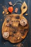 Muffins σοκολάτας με την κρέμα και χάντρες σε έναν παλαιό ξύλινο τέμνοντα πίνακα επάνω από την όψη Στοκ εικόνες με δικαίωμα ελεύθερης χρήσης