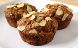Muffins. Three fruit and nut muffins topped with sliced almonds royalty free stock images