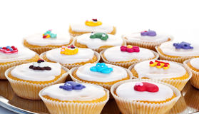 Muffins. With glaze and edible toy figures on a plate, isolated on white Stock Photography