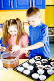 Muffins. Young boy and girl making chocolate muffins Royalty Free Stock Photos