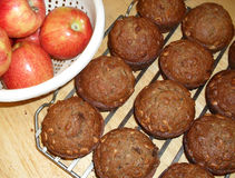 Muffins and apples. Big warm muffins and red apples on table royalty free stock images
