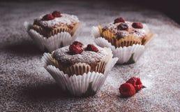 Muffins auf einem Holztisch bedeckt mit Zucker Stockbilder